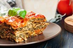 Stycke av smakliga varma lasagner med spenat på en platta Royaltyfria Foton