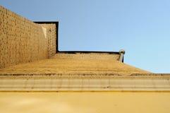 Stycke av tegelstenhusväggen med klar himmel på bakgrunden Royaltyfria Bilder