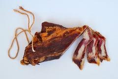 Stycke av torkad bacon med det hängande repet och några skivor på neutralt bakgrundsslut upp arkivfoto