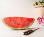 Stycke av vattenmelon på den vita tabellen med kniven Saftig uppfriskande sommarmat royaltyfri foto