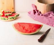 Stycke av vattenmelon på den vita tabellen på väggbakgrund med kniven Saftig uppfriskande sommarmat kopiera avst?nd arkivfoto