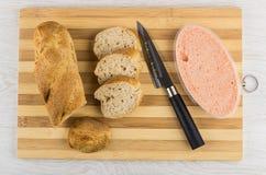Stycken av bröd, kniv, kaviar i krus på skärbräda royaltyfri fotografi