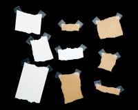 Stycken av brevpapper på svart bakgrund Arkivbilder