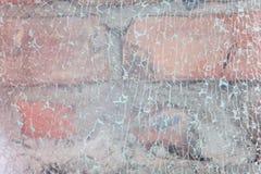 Stycken av brutet exponeringsglas på väggmakroen royaltyfri bild