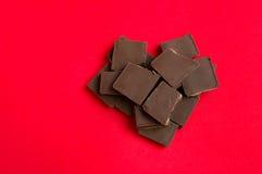 Stycken av choklad i hjärta formar på röd bakgrund Arkivbilder
