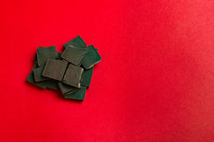 Stycken av choklad i hjärta formar på röd bakgrund Royaltyfri Fotografi