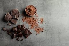 Stycken av choklad- och kakaopulver på grå bakgrund royaltyfria foton