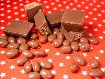 Stycken av choklader på röd bakgrund Royaltyfri Fotografi