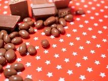 Stycken av choklader på röd bakgrund Arkivfoto