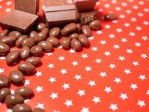 Stycken av choklader på röd bakgrund Royaltyfri Foto