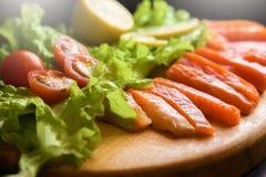 Stycken av den röda fisken med citronen och körsbärsröda tomater arkivfoto