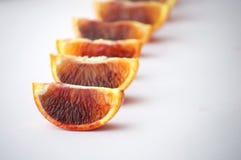 Stycken av den smakliga saftiga blodapelsinen på vit bakgrund Horisont Fotografering för Bildbyråer
