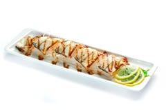 stycken av den vita fisken med citronen och örter på en platta på en isolerad vit bakgrund arkivbilder