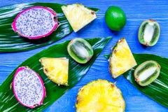 Stycken av exotiska frukter Dragonfruit, ananas och kiwi på bästa sikt för blå träbakgrund Arkivbilder