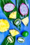 Stycken av exotiska frukter Dragonfruit, ananas och kiwi på bästa sikt för blå träbakgrund Fotografering för Bildbyråer