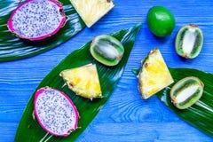 Stycken av exotiska frukter Dragonfruit, ananas och kiwi på blå träcopyspace för bästa sikt för bakgrund Arkivfoton