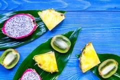 Stycken av exotiska frukter Dragonfruit, ananas och kiwi på blå träcopyspace för bästa sikt för bakgrund Arkivbilder