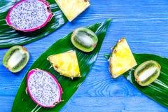 Stycken av exotiska frukter Dragonfruit, ananas och kiwi på blå träcopyspace för bästa sikt för bakgrund Royaltyfri Bild