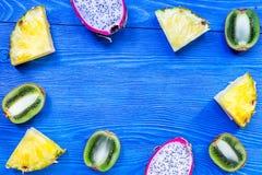 Stycken av exotiska frukter Dragonfruit, ananas och kiwi på blå träcopyspace för bästa sikt för bakgrund Arkivbild