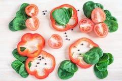 Stycken av grönsaker, tomater, peppar, sallad på en träbackg royaltyfri bild