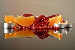 Stycken av granatäpple- och apelsinkilar med stearinljus fotografering för bildbyråer