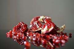 Stycken av granatäpplet reflekterade i exponeringsglaset arkivfoton