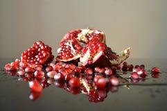 Stycken av granatäpplet reflekterade i exponeringsglaset royaltyfri fotografi