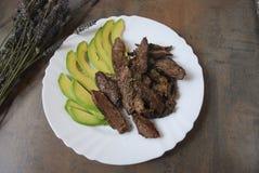 Stycken av grillad nötköttbiff med avokadot Arkivfoton