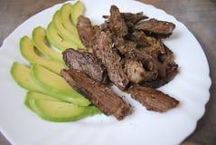 Stycken av grillad nötköttbiff med avokadot Royaltyfria Foton