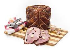 Stycken av griskött på en skärbräda Arkivfoto