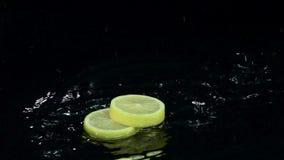 Stycken av gul citrondroppe in i vattnet Svart bakgrund långsam rörelse arkivfilmer