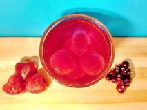 Stycken av isfruktsaftflötet i exponeringsglas med vatten royaltyfri bild