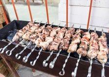 Stycken av kött på steknålar som stekas på gallret fotografering för bildbyråer