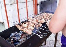 Stycken av kött på steknålar som stekas på gallret arkivbilder