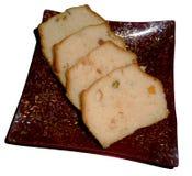 Stycken av kakan med frukter på plattan som isoleras Fotografering för Bildbyråer