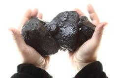 Stycken av kol i handen som isoleras på vit bakgrund royaltyfri foto