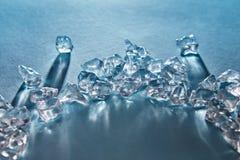 Stycken av krossade iskuber i i form av en båge med långa skuggor och reflexioner på yttersidan på en blått arkivfoto