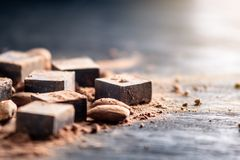 Stycken av mörk bitter choklad med kakao- och mandelmuttrar på träbakgrund Kort med utrymme för text arkivbild