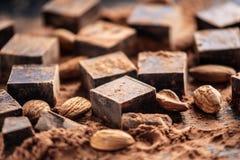 Stycken av mörk bitter choklad med kakao- och mandelmuttrar på träbakgrund Kort med utrymme för text royaltyfri fotografi