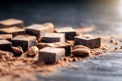 Stycken av mörk bitter choklad med kakao- och mandelmuttrar på träbakgrund Kort med utrymme för text royaltyfri bild