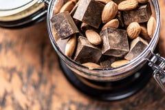 Stycken av mörk bitter choklad med kakao och tokiga mandlar på träbakgrund Begrepp av konfektingredienser arkivfoton