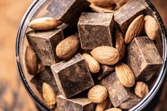 Stycken av mörk bitter choklad med kakao och tokiga mandlar på träbakgrund Begrepp av konfektingredienser arkivfoto