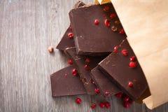 Stycken av mörk choklad med rosa färgpeppar Fotografering för Bildbyråer