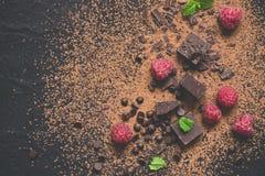 Stycken av mörka choklad, pulver, droppar och hallon Matefterrättbakgrund Royaltyfri Fotografi