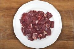 Stycken av nötkött på en vit platta Arkivbild
