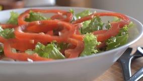 Stycken av nedgången för söt peppar på en vegetarisk sallad i en vit bunke Clouse upp lager videofilmer