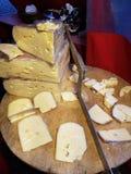 Stycken av ost på en träklipptabell och en special kniv-grymtning Royaltyfri Bild