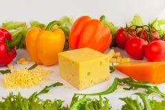 Stycken av ostar av olika smaker, grated ost, nya tomater, peppar och sidor av frillis och arugula Royaltyfri Bild