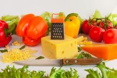 Stycken av ostar, grated ost, belägger med metall spisgallret, kniven, tomater, peppar och sidor av frillis och arugula Arkivbild