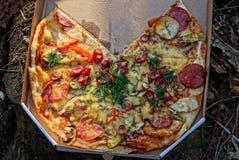 Stycken av pizza i en gr? pappers- ask royaltyfri fotografi